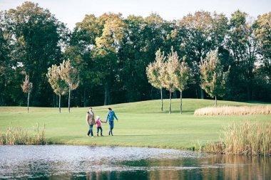 Happy family walking near lake