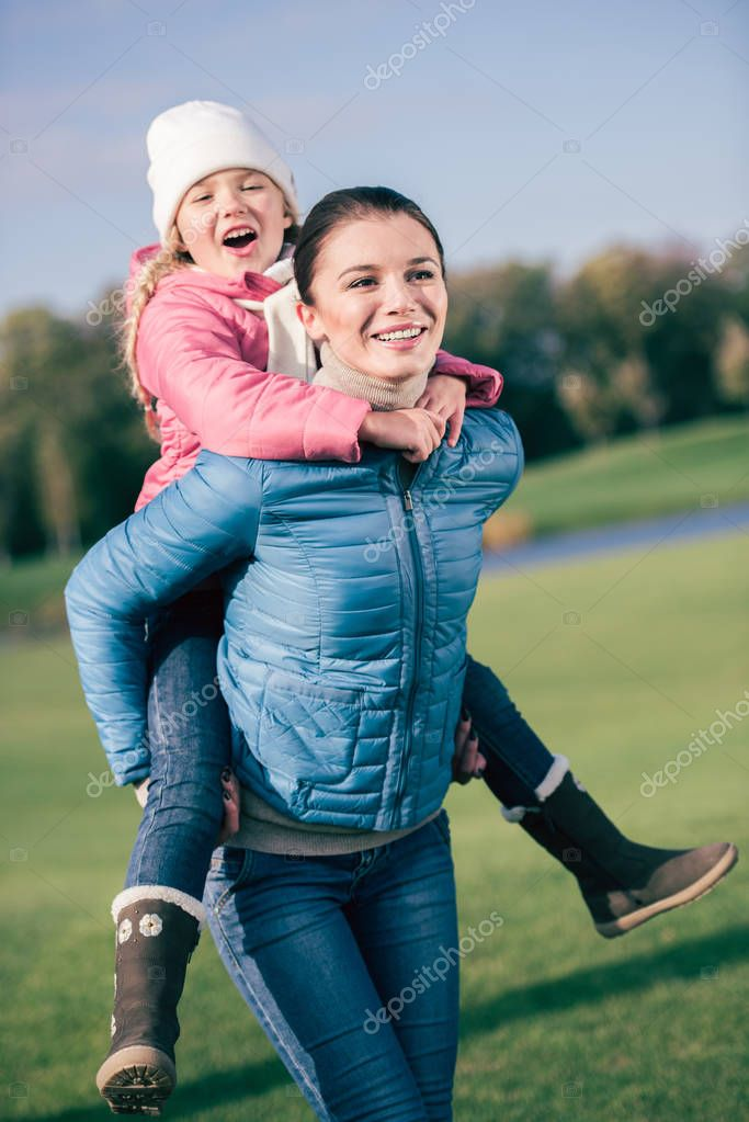 Cheerful mother piggybacking little daughter