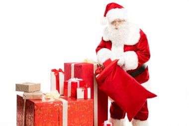 Happy Santa Claus taking out Christmas gifts from a big sack isolated on white stock vector