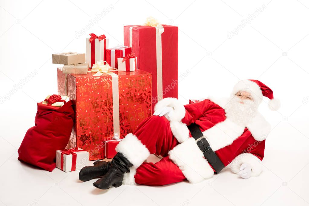 Santa Claus near pile of Christmas gifts