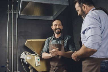 Smiling male workers in aprons looking at each other at brewery stock vector