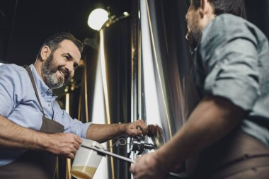 Brewery workers pouring beer