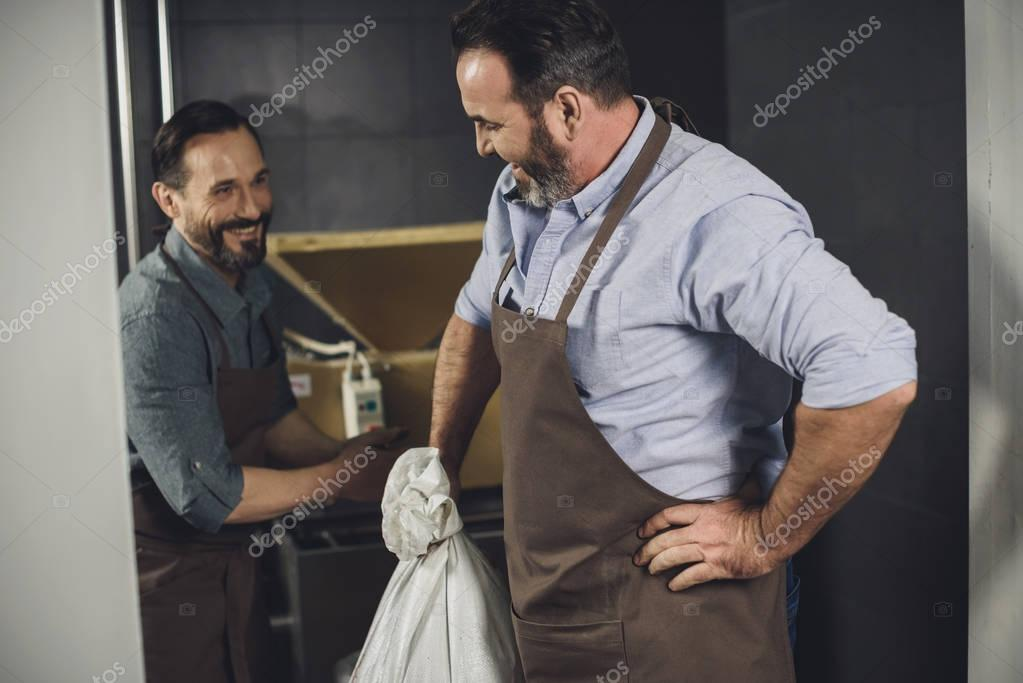 Male brewery workers in aprons