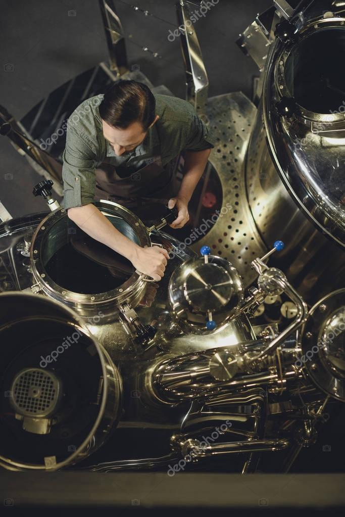 Brewer inspecting tank