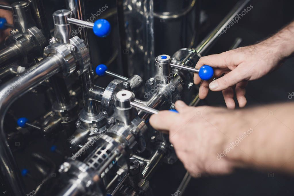 Brewer working with industrial equipment