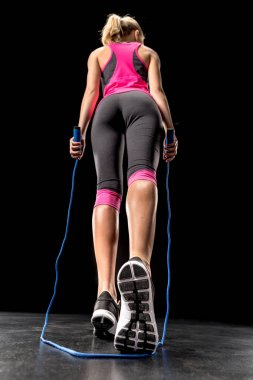 Sportswoman exercising with skipping rope