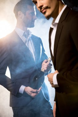 Stylish men with champagne bottle