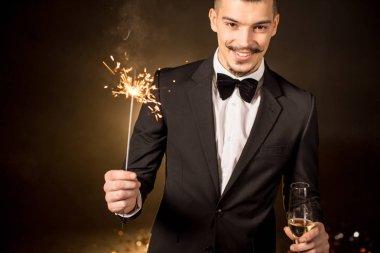 Handsome man holding sparkler