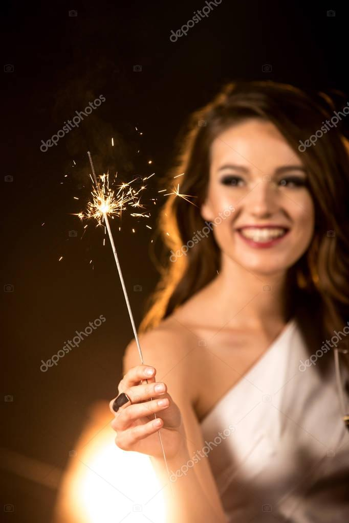 Beautiful woman holding sparkler