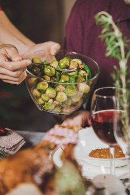 Woman putting brussel sprouts on plate