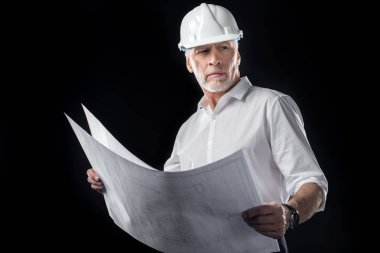 Mature male architect in white hard hat holding blueprints and looking away  isolated on black stock vector