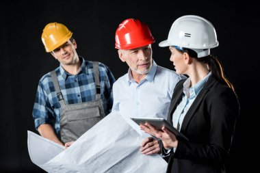 Two architects in hard hats chatting over blueprint while engineer waiting stock vector
