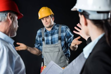 Two angry architects blaming engineer in hard hat on black stock vector