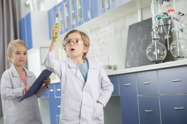 Preteen schoolboy in lab coat looking at sample in test tube stock vector