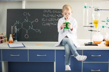 Schoolgirl holding flask with sample