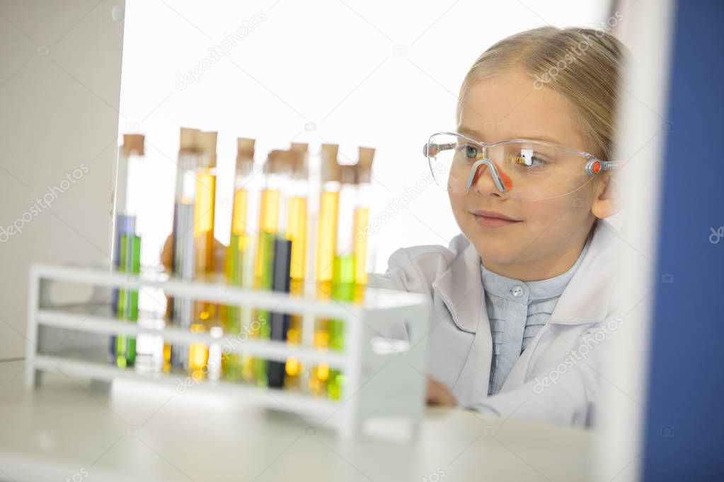 Schoolgirl looking at test tubes