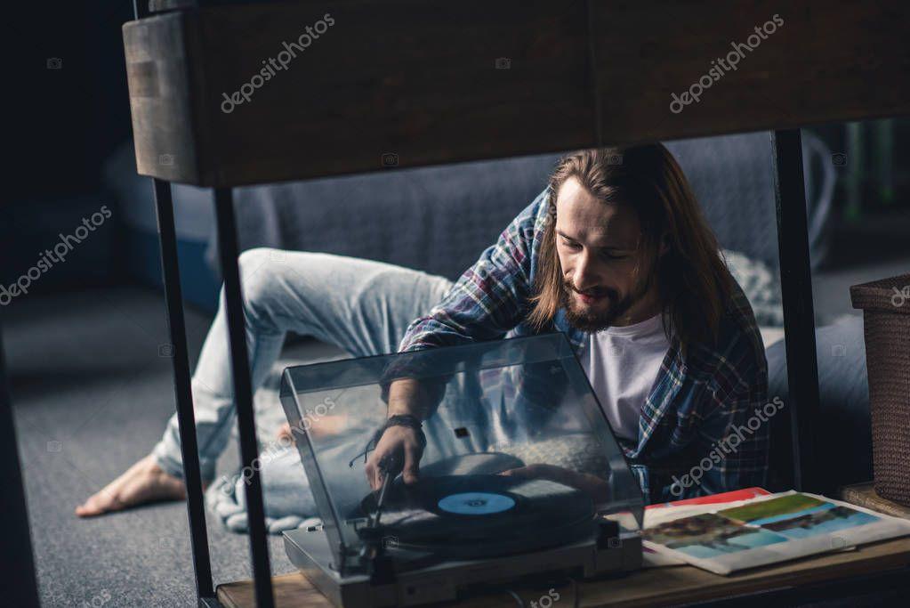 Man putting vinyl record on turntable