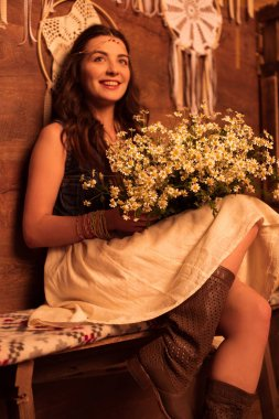 bohemian woman sitting with bouquet of chamomiles