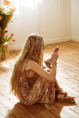 Woman in boho style using smartphone
