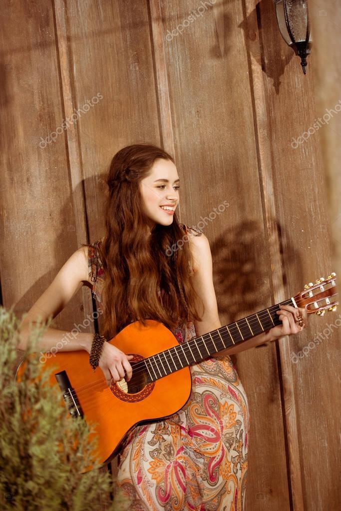 Young smiling bohemian woman with long hair playing guitar