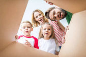 Photo Family peeking from cardboard box