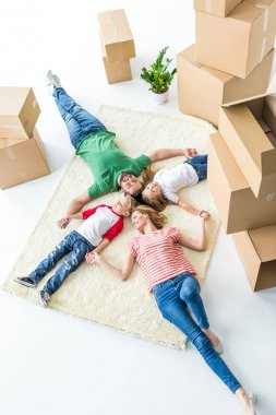 Top view of young family of four relaxing on carpet after moving into new house isolated on white stock vector