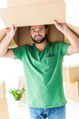 Young man peeks from cardboard box on his head and smiling at camera isolated on white stock vector