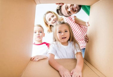 Family peeking from cardboard box