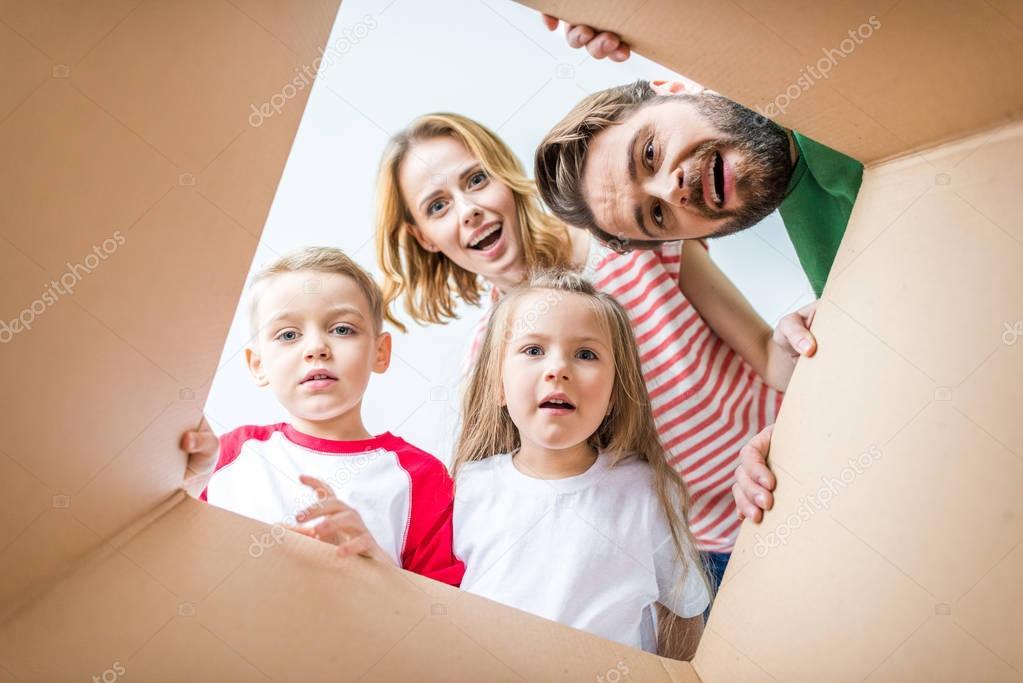 Family peeking from cardboard box