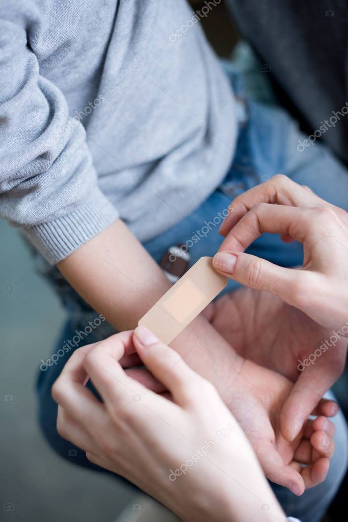 Doctor putting medical patch on hand