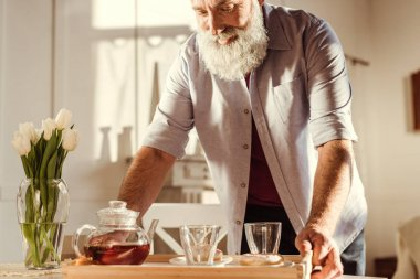 Man holding tray with tea