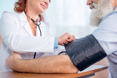Female doctor measuring pressure of senior male patient in hospital stock vector
