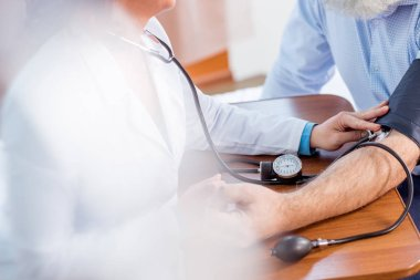Doctor measuring pressure of patient