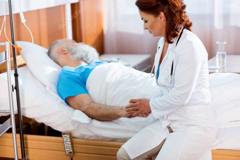 Doctor holding hand of patient