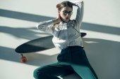 stylische Hipster-Frau mit Skateboard