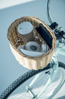 basket with coffee cup and headphones