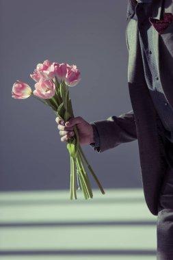 stylish man holding tulips