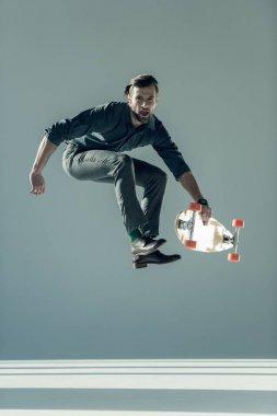 fashionable man holding skateboard