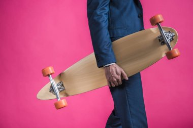 man in suit with skateboard