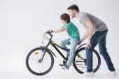 otec pomáhal syn jezdit na kole