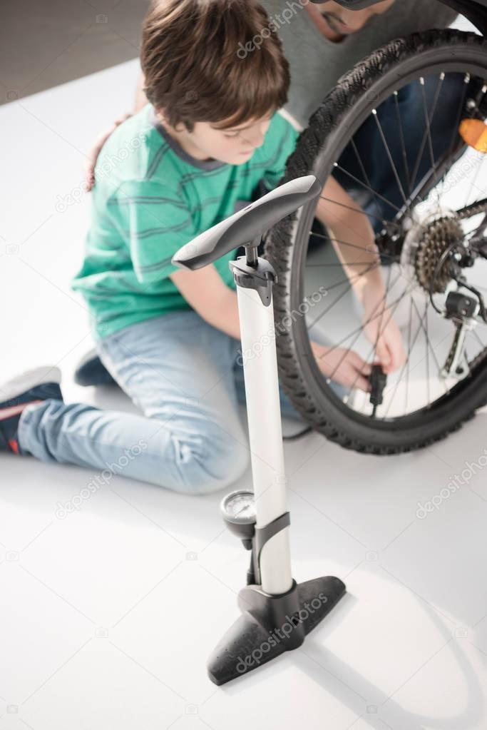 Father and son inflating bicycle tire