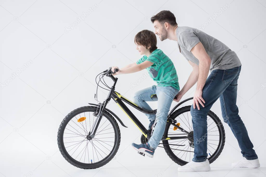father helping son to ride bicycle