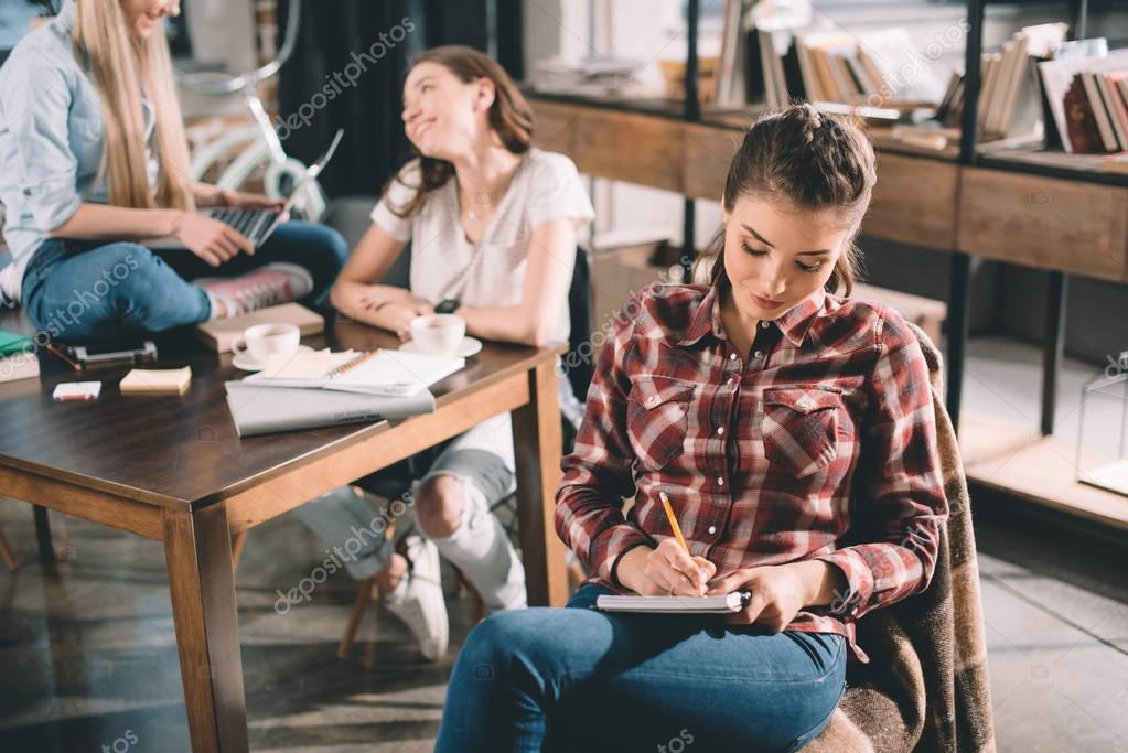woman studying and writing in copybook