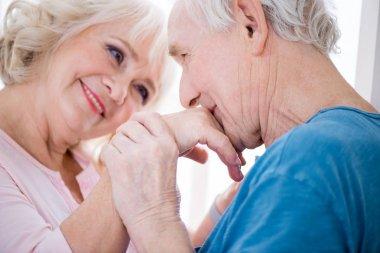 Portrait of happy senior couple, man kissing hand. stock vector