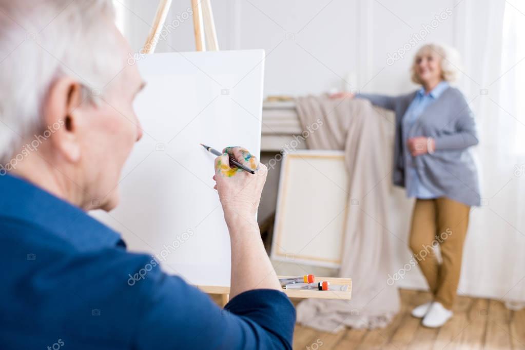 man drawing portrait of woman