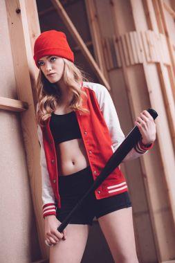 Stylish hipster woman in baseball jacket with black baseball bat stock vector