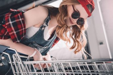 Smiling young woman with cap and sunglasses standing with shopping cart stock vector