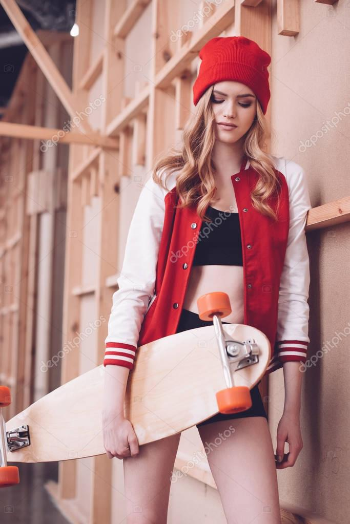 Stylish hipster woman in baseball jacket with longboard posing at wooden wall stock vector