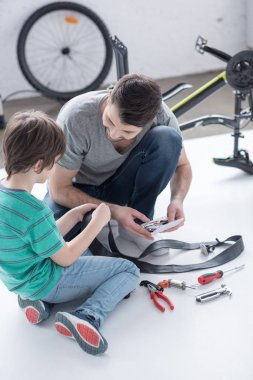 father and son repairing bicycle tire