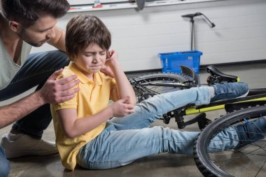 Father and son falling off bike